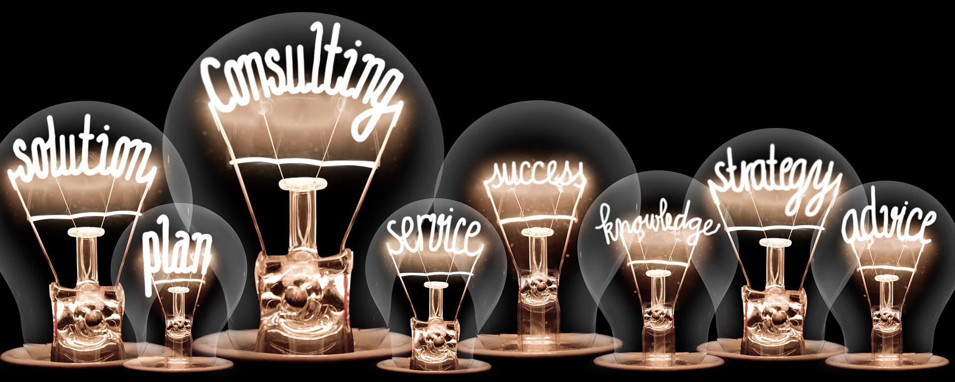 Photo of light bulbs with shining fibers in a shape of CONSULTING concept related words isolated on black background
